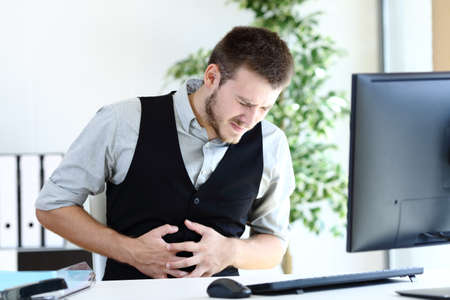 Young executive man suffering belly ache sitting at office