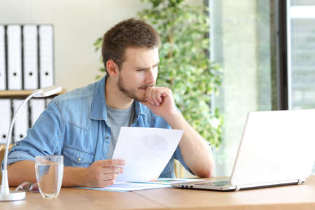 Pensive man holding document reading laptop content working at office