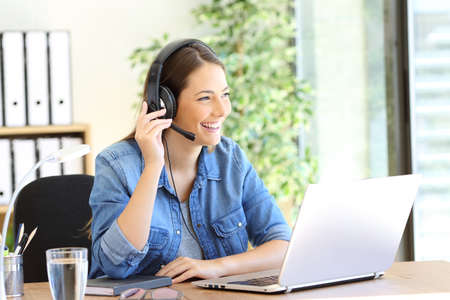 Happy tele operator woman attending call looking away at office