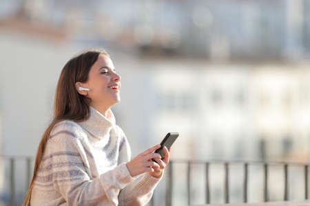 Happy woman listens to music with wireless earbuds and smart phone in a balcony in winter
