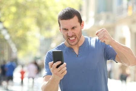 Front view portrait of an angry man checking crashed smart phone standing in the street Stock fotó