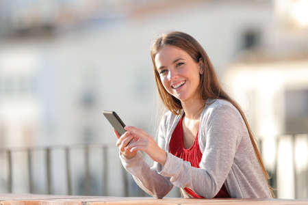 Happy woman looks at camera holding mobile phone in a balcony a suny day Stockfoto