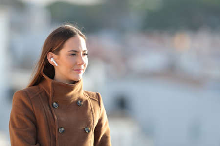 Relaxed woman listening to music using wireless earphones looking away in winter