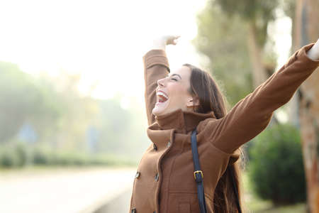 Excited happy woman wearing jacket celebrating success in winter in a park