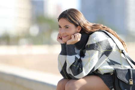 Beauty girl wearing jersey sitting looking away in the street in winter