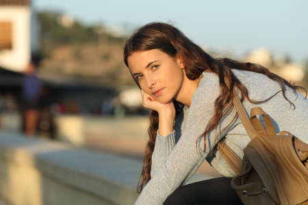 Serious casual girl looks at you at sunset sitting in the street