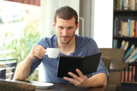 Ritratto vista frontale di un uomo serio che legge un ebook seduto in una caffetteria
