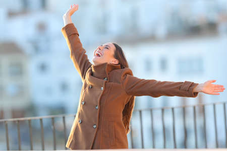 Excited woman wearing jacket raising arms in winter in a balcony