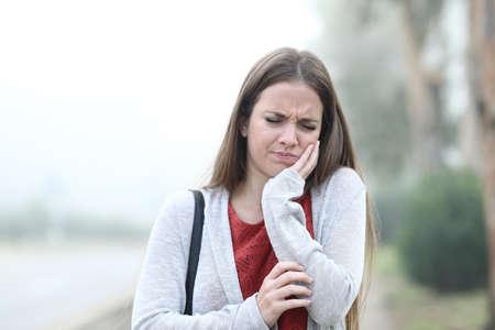 Vorderansichtporträt einer frau, die an einem nebligen tag unter zahnschmerzen leidet