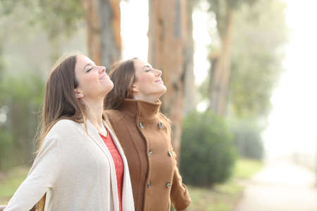Two relaxed women breathing deeply fresh air standing in a park Stockfoto