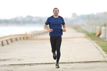 Runner training running towards camera on a concrete way