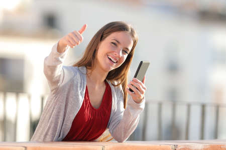 Happy girl holding mobile phone with thumbs up in a balcony a sunny day