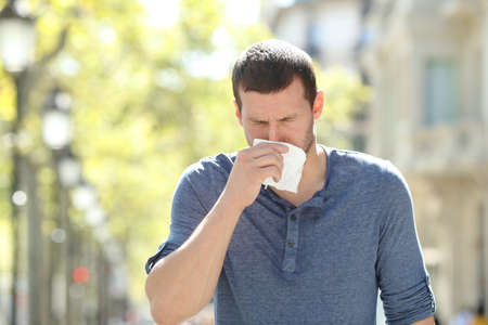 Front view portrait of an Ill adult man blowing using a tissue in the street