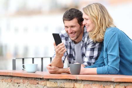 Happy adult couple checking smart phone standing outdoors in a balcony in a rural town