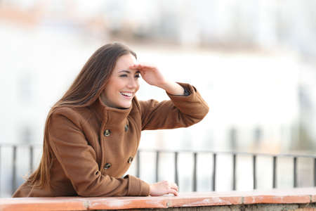 Happy woman looking forward with hand on forehead in a balcony in winter Stockfoto