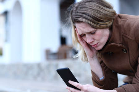 Sad adult woman complaining reading bad news on mobile phone in the street in winter