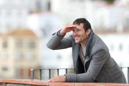 Happy man contemplating with hand on forehead standing in a balcony outdoors in a rural town