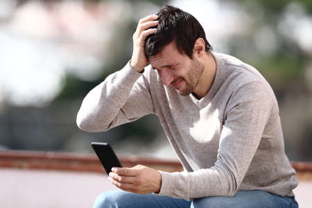 Worried man checking mobile phone complaining after mistake outdoors in a rural town