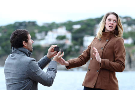 Shocked girlfriend rejecting marriage proposal of a sad man on the beach in winter