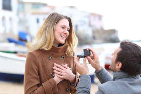 Man proposing marriage and happy girlfriend accepting in winter holiday on the beach