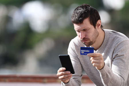 Worried man buying online with credit card and smart phone sitting in a rural town