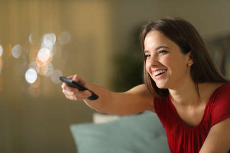 Happy girl watching tv using remote control in the night sitting on a couch in the living room at home Stock Photo