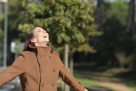 Happy woman is breathing fresh air in winter standing in a park a sunny day