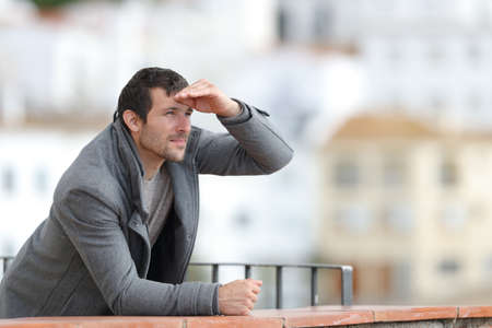 Man contemplating with hand on forehead standing in a balcony outdoors in a rural town