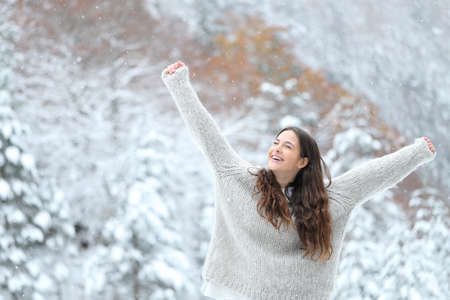 Excited girl raising arms enjoying snow in winter in the mountain