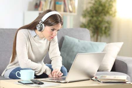 E-learning de chica seria con ordenador portátil y auriculares sentado en un sofá en la sala de estar en casa Foto de archivo