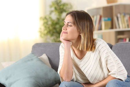Relaxed woman meditating sitting on a couch in the living room at home
