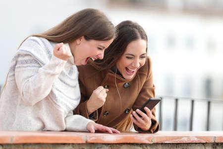 Aufgeregte Frauen, die im Winter auf einem Balkon in einer ländlichen Stadt Handynachrichten überprüfen Standard-Bild