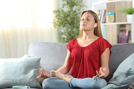 Donna che pratica esercitazione sull'ascolto dello yoga con auricolari wireless seduta su un divano nel soggiorno di casa