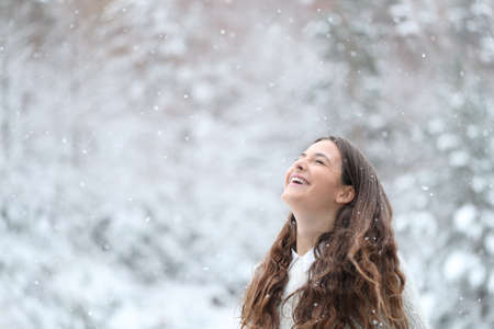 Happy girl breathing fresh air laughing enjoying snow in winter in the mountain