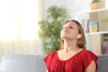 Satisfied woman meditating breathing fresh air using wireless earphones sitting on a couch in the living room at home
