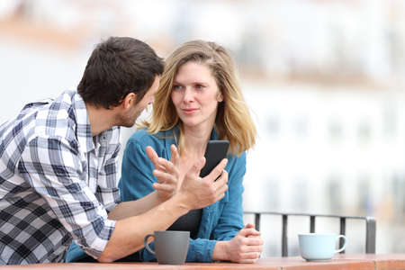 Serious couple talking about mobile phone content standing outdoors in a balcony in a rural town