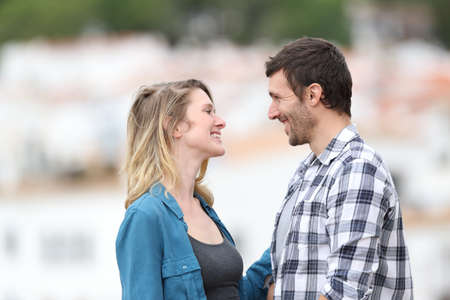 Profile of a couple flirting looking each other standing outdoors in a rural town