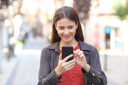 Vue de face portrait d'un adolescent heureux vérifiant le contenu du téléphone portable marchant dans la rue