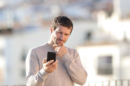 Doubtful adult man checking smart phone content standing in a rural town