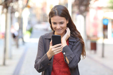 Vue de face portrait d'un adolescent candide vérifiant le texte d'un téléphone intelligent marchant dans la rue