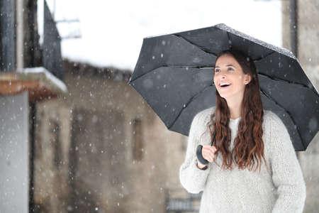 Happy girl under umbrella enjoying snow fall in winter in a town