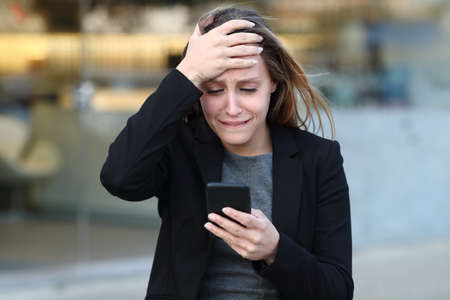 Front view of a sad executive complaining checking smart phone in the street beside office