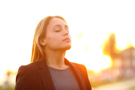 Serious businesswoman breathing fresh air at sunset standing outdoors