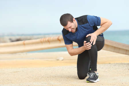 Painful runner complaining suffering knee ache after sport on the beach
