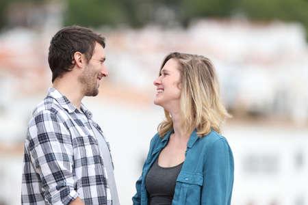 Ritratto di vista laterale di un uomo e di una donna che si guardano innamorarsi in una città