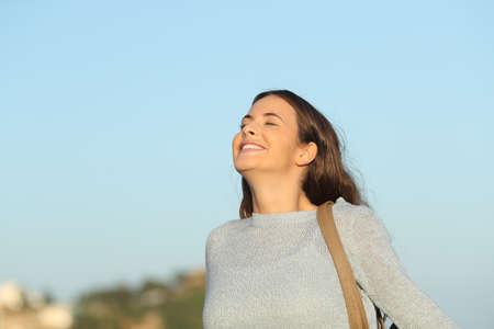 Femme heureuse respirant profondément l'air frais avec un ciel bleu en arrière-plan