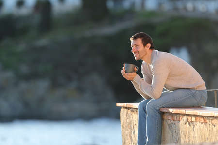 Happy man drinking coffee contemplating views sitting in a balcony outdoors in a coast town