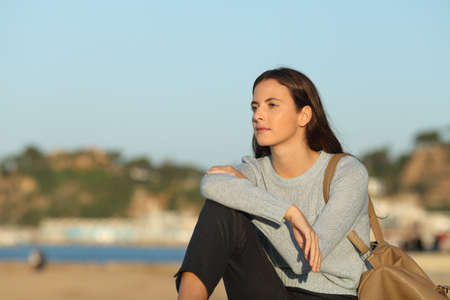 Confident woman looking away sitting in a coast town beach