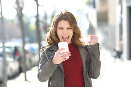 Front view portrait of an excited girl checking smart phone news in the street