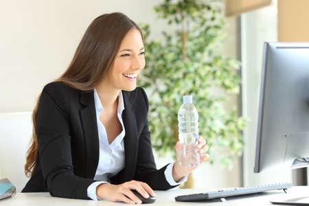 Ejecutivo feliz trabajando sosteniendo una botella de agua usando la computadora en la oficina